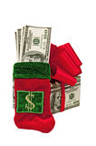 Gifts of Money. A Christmas stocking filled with money leans against a Christmas present made of money.  Isolated on white Stock Images