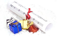 Gifts and music. Gifts and chrstmas music on snow Royalty Free Stock Photos