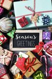 Gifts, ornaments and text seasons greetings. High angle view of some christmas ornaments, cookies, a pile of gifts tied with ribbons of different colors, and a royalty free stock image