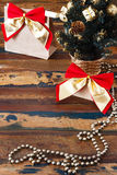 Gifts  package with red golden bow near small Christmas tree Stock Image