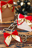 Gifts package with red golden bow near small Christmas tree Royalty Free Stock Photos