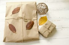 Gifts packaged in craft paper and dry autumn leaves royalty free stock photos