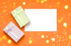 Gifts and a piece of paper for the inscription on an orange background with Christmas lights stock photos