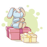 Gifts and plushy rabbit. Sitting on it Royalty Free Stock Photography