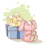 Gifts and plushy rabbit. Sitting near it Royalty Free Stock Photography