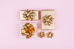 Gifts or presents boxes with golden bows on pink pastel background top view. Flat lay for birthday, christmas or wedding. stock photography