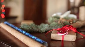 Gifts, presents and packaging materials: wrapping paper, fir tree branches, cones and ribbons on table. Fireplace. Decorated with garland lights on background stock video