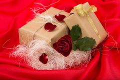 Gifts with red rose on red satin Royalty Free Stock Photo