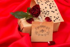Gifts with red rose on red satin Royalty Free Stock Photography