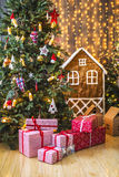 Gifts in red and white packaging under the green Christmas tree decorated with Christmas toys and candles Royalty Free Stock Photo
