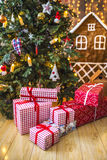 Gifts in red and white packaging under the green Christmas tree decorated with Christmas toys and candles Stock Photo