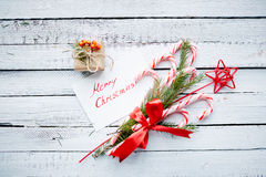 Gifts and regards. Christmas bouquet, greeting card and small giftbox on wooden background Royalty Free Stock Photography