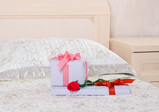 Gifts and a rose. Beautiful gift box and red rose on the bed Stock Photography