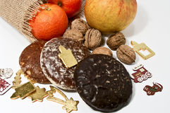 Gifts from Santa Claus. Gingerbread cookies, nuts, an apple and tangerines Stock Photos