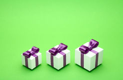 Gifts with satin bows on green Stock Photo