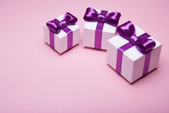 Gifts with satin bows on a pink background Stock Images