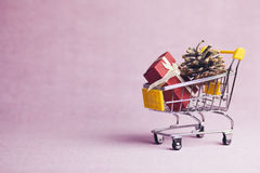 Gifts on shopping cart. Shopping cart full of gift box on pink background Royalty Free Stock Images