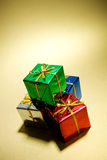 Gifts: Stack Of Miniature Christmas Gifts On Gold. Series of miniature, colorful gift boxes, some on colored backgrounds, some on white Royalty Free Stock Photo
