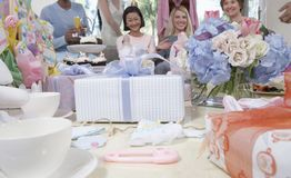 Gifts On Table At A Baby Shower. Happy women at a baby shower with gifts on table in foreground Royalty Free Stock Images