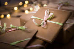 Gifts on the table. Gifts wrapped with the gray paper. Christmas lights blurred in the background Stock Photo