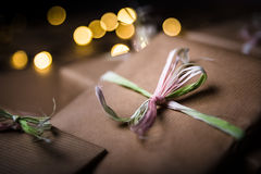 Gifts on the table. Gifts wrapped with the gray paper. Christmas lights blurred in the background Stock Photos