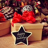 Gifts and text happy holidays in a star-shaped chalkboard. The text happy holidays written in a star-shaped chalkboard with some gifts and a pile of different Stock Images