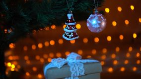 Gifts under a christmas tree against a background of garland at night, close-up. Christmas tree with multi-colored balls and toys from below gift boxes on a stock video footage