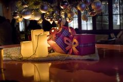 Gifts under Christmas tree in ambient living room with fireplace. N royalty free stock images