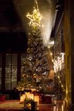 Gifts under Christmas tree in ambient living room with fireplace. N royalty free stock image