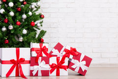 Gifts under decorated christmas tree with colorful balls over br Royalty Free Stock Photo