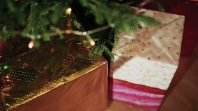 Gifts under a decorated Christmas tree stock video footage