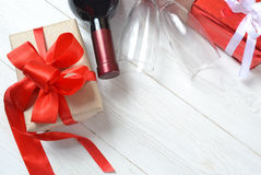 Gifts, wine, two glasses on the table. Royalty Free Stock Photos