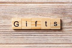 Gifts word written on wood block. gifts text on table, concept.  Stock Image