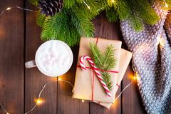 Gifts wrapped with craft paper, decorated with candy cane and cup mug of coffee cacao on a rustic dark wooden table with stock photography