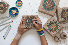 Gifts wrapped in kraft paper. On boxes painted mandala pattern. Stock Photo