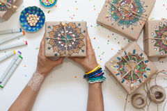 Gifts wrapped in kraft paper. On boxes painted mandala pattern. Royalty Free Stock Photography