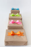 Gifts wrapped in kraft paper. Coloured bright paper bows. Stock Image