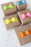 Gifts wrapped in kraft paper. Coloured bright paper bows. Royalty Free Stock Photography