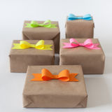 Gifts wrapped in kraft paper. Coloured bright paper bows. Stock Images