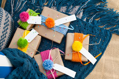 Gifts wrapped in kraft paper lie on a knitted rug. Stock Images