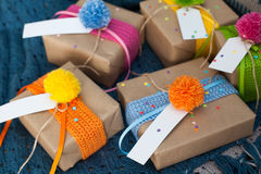 Gifts wrapped in kraft paper lie on a knitted rug. Stock Photo