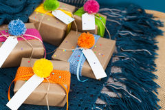Gifts wrapped in kraft paper lie on a knitted rug. Royalty Free Stock Photography