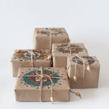 Gifts wrapped in kraft paper. The packaging ornament mandala. Stock Photo