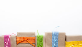 Gifts wrapped in kraft paper and tape knitted from yarn. Royalty Free Stock Photography