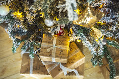 Gifts wrapped in paper under a green tree and white ends of the needles. Royalty Free Stock Images