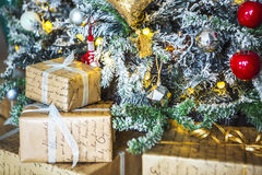 Gifts wrapped in paper under a green tree and white ends of the needles. Stock Photos