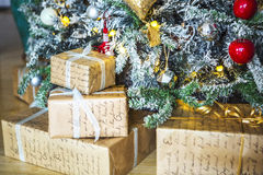 Gifts wrapped in paper under a green tree and white ends of the needles. Royalty Free Stock Photos