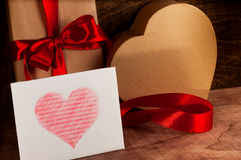 Gifts wrapped with a red ribbon and cardboard heart. White card with a red heart.Valentine's day Royalty Free Stock Photo