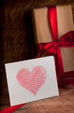 Gifts wrapped with a red ribbon. White card with a red heart.Valentine's day Royalty Free Stock Photos