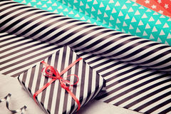 Gifts and wrapping paper on white wooden background. Stock Image